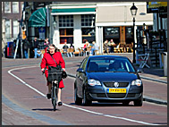 Elderly woman riding bike along a car, Amsterdam, Holland, The Netherlands, Europe