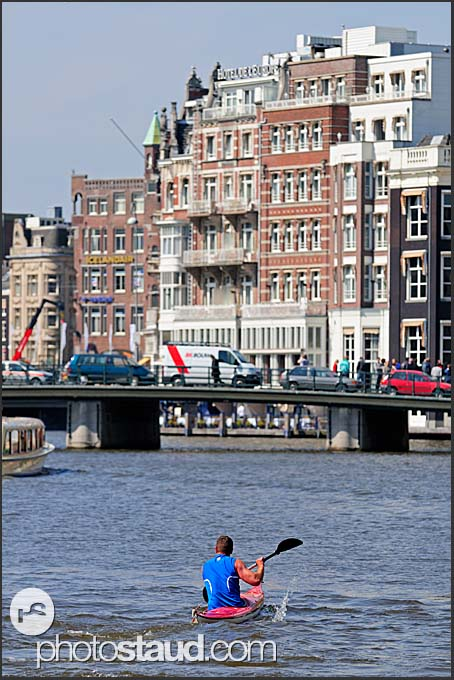 Kayaker paddling through Amsterdam, Amsterdam, Holland, The Netherlands, Europe