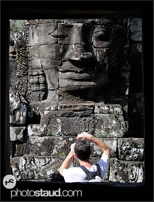 Tourist taking photograph of Lokeshvara statue, Bayon Temple, Angkor Thom, Cambodia