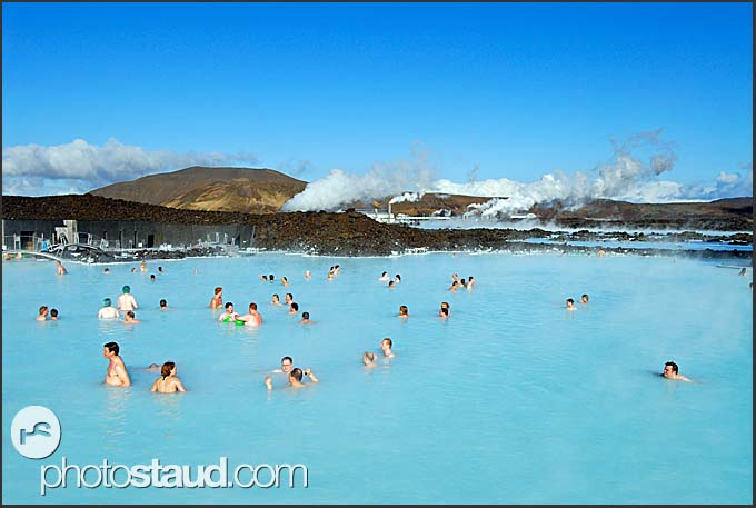 People enjoying sunny day in Blue Lagoon, Svartsengi power plant in background, Iceland