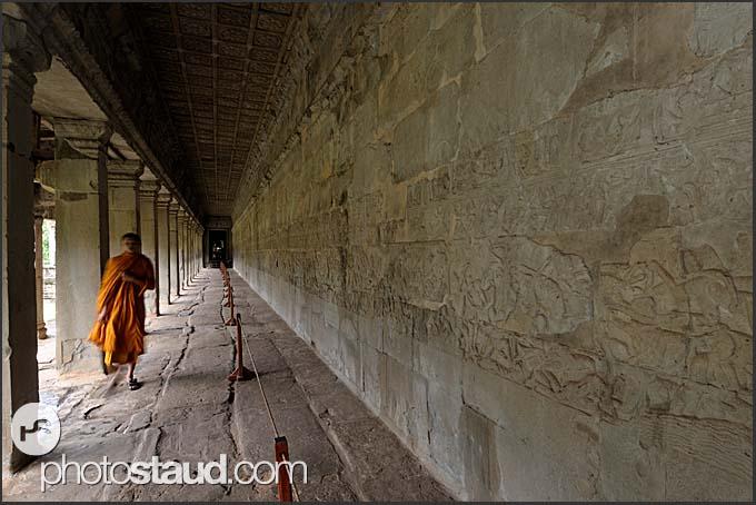 Buddhist monk walking along the bas relief walls of Angkor Wat, Cambodia