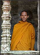 Buddhist monk standing in stone window of Angkor Wat, Cambodia