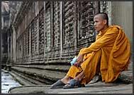 Buddhist monk in orange robe walking along the bas reliefs in Angkor Wat, Cambodia