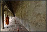 Buddhist monk inspects the bas reliefs of Angkor Wat, Cambodia