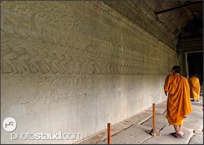 Buddhist monks inspecting the bas relief walls of Angkor Wat, Cambodia