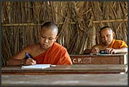Two Buddhist monks sitting in open air school, Bakong monastery, Angkor, Cambodia