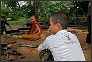 Buddhist monk apprentice in a playboy shirt cutting woods, Bakong monastery, Angkor, Cambodia