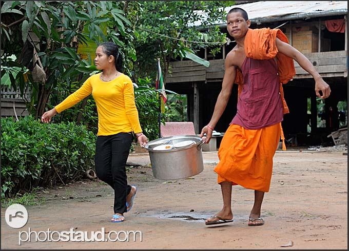 Buddhist monk with a girl carrying dishes in Lolei Temple, Angkor, Cambodia
