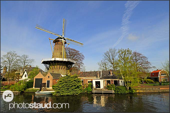 Traditional Dutch windmill along canal, Holland, Europe