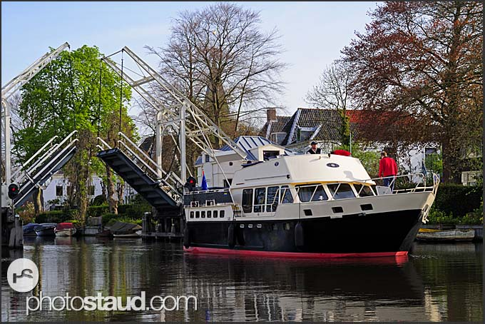Yacht passing through open bridge on Dutch canal, Holland, Europe