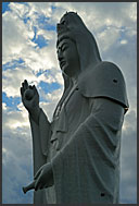 Sun setting behind Gigantic Buddhist statue of the bodhisattva Dai-Kannon, Sendai, Japan