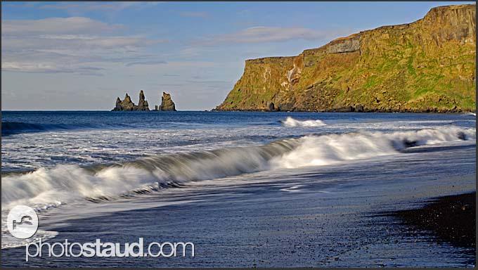 Seascape of the south coast near Dyrholaey, black lava columns of the Reynisdrangar in background, Iceland