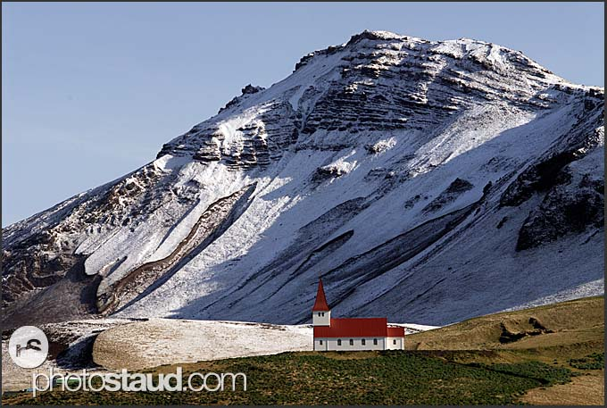 Isolated church of Vik on the south coast with snowy mountains behind, Iceland