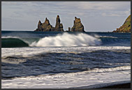 White waves of the Atlantic Ocean with black lava columns of the Reynisdrangar coming out of the sea, Iceland