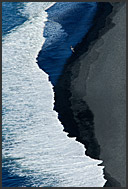 White waves and volcanic black sand, couple walking on Atlantic Ocean beach, aerial view, southern Iceland