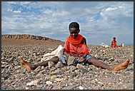 Children of El Molo tribe work hard breaking shore stones to build a fish storage house in their village, Lake Turkana, Northern Kenya