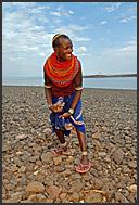El Molo people work hard breaking shore stones to build a fish storage house in their village, Lake Turkana, Northern Kenya