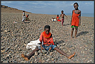 El Molo people work hard breaking shore stones to build a fish storage house in their village, Lake Turkana, Northern Kenya