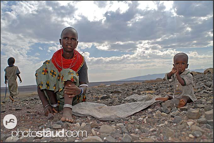 Children of El Molo tribe work hard breaking shore stones to build a fish storage house in their village, Lake Turkana, Northern Kenya