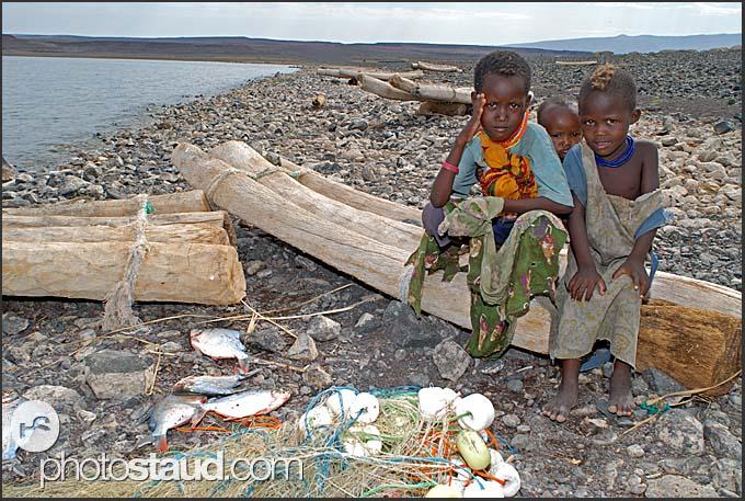 El Molo children resting on palm tree rafts after fishing, Lake Turkana, Northern Kenya