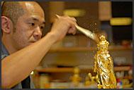 Decorating Buddha statue with golden leaves of Kanazawa, Japan