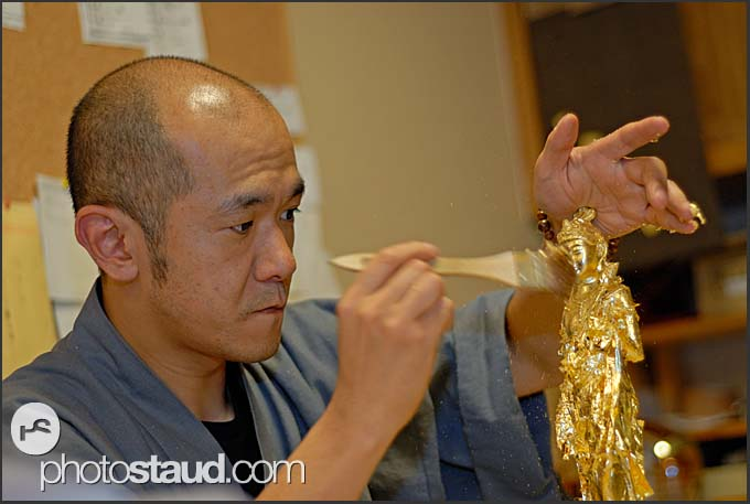 Decorating Buddha statue with golden leaves of Kanazawa, Japan