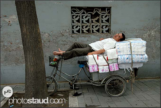 Chinese man having a nap on his tricycle in the old streets of Hutong, Beijing, China