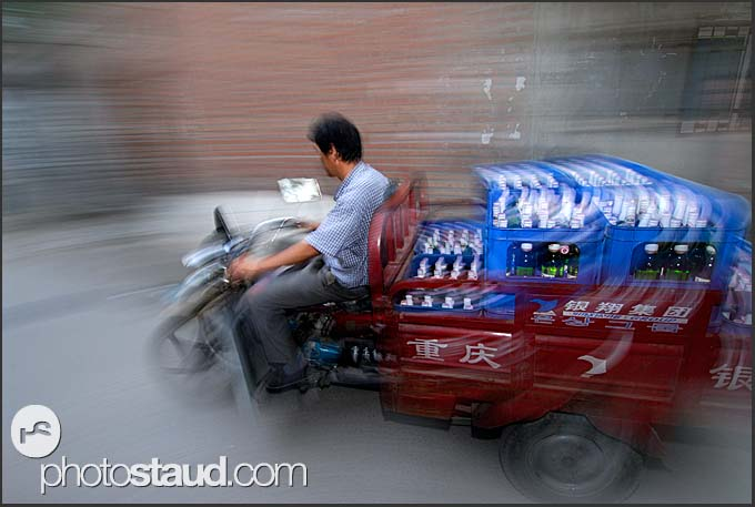 Beijing Hutong in motion - Chinese man transporting bottled beer on his tricycle, China