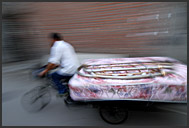 Beijing Hutong in motion - Chinese man transporting bed on his tricycle, China