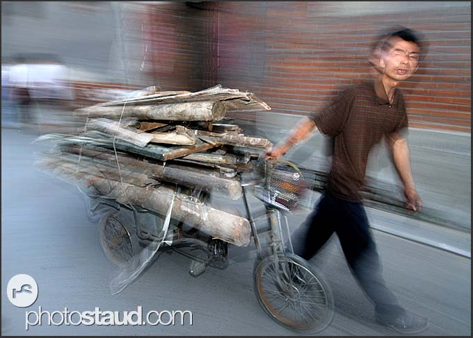 Beijing Hutong in motion - Chinese man transporting fire wood on his tricycle, China