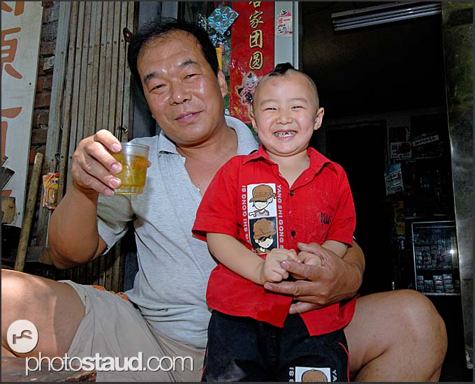 Chinese man and grandson drinking tea outside courtyard house in a Beijing Hutong, China