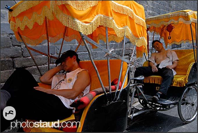 Riders resting in their rickshaws, Beijing Hutong, China