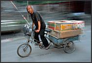 Rickshaw rider talks to his customer on the way through narrow lanes of Beijing Hutong, China