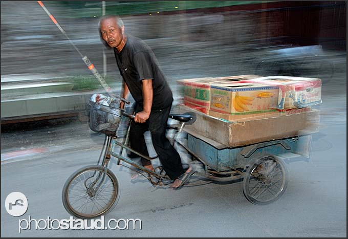 Beijing Hutong in motion - Chinese man transporting cardboard boxes on his tricycle, China