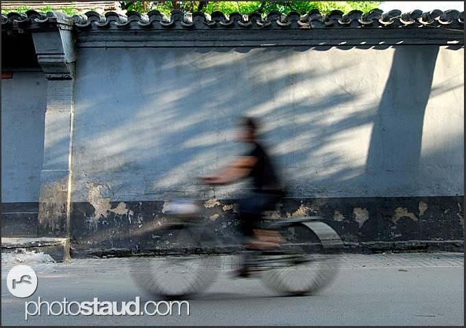 Cyclist riding in Beijing Hutong, China