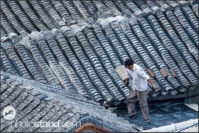 Chinese man repairing his roof in Beijing Hutong, China