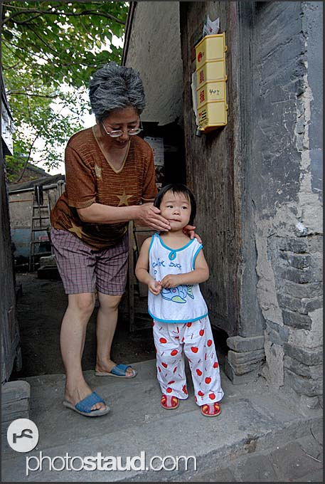 Little Chinese girl with her granny in the narrow lanes of Beijing Hutong, China