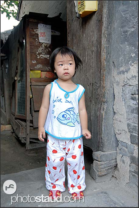 Little Chinese girl with in the narrow lanes of Beijing Hutong, China