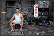 Elderly Chinese man repairing bicycles in the streets of Beijing Hutong, China