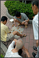Men playing Chinese chess on the ground in Beijing Hutong, China