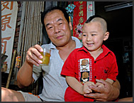 Chinese man drinking tea outside his courtyard house in a Beijing Hutong, China