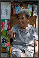 Senior Chinese woman sitting outside her courtyard house in a Beijing Hutong, China