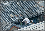 Chinese couple repairing their roof in Beijing Hutong, China