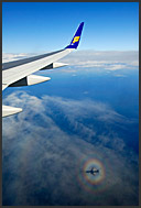 On the wings of Iceland Air - with a plane shadow projected on the clouds below, Iceland