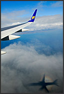 Passenger view from Iceland Air plane flying above Iceland - plane shadow projected on the clouds below, Iceland