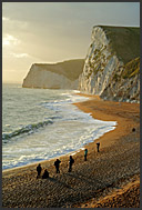 Group of tourists watching sunset over the Atlantic Ocean with white chalk cliffs in the back, Jurassic Coast, Dorset, England, Europe