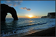 Durdle Door natural limestone arch at sunset, chalk cliffs of Bat's Head and Swyre Head in the back, Jurassic Coast, Dorset, England, Europe