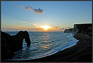 Sun setting behind Durdle Door natural limestone arch, Jurassic Coast World Heritage site, Dorset, England, Europe