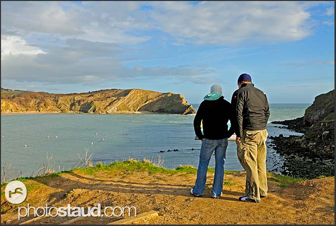 Tourists reading information panel at Lulworth Cove, Jurassic Coast World Heritage site, Dorset, England, Europe