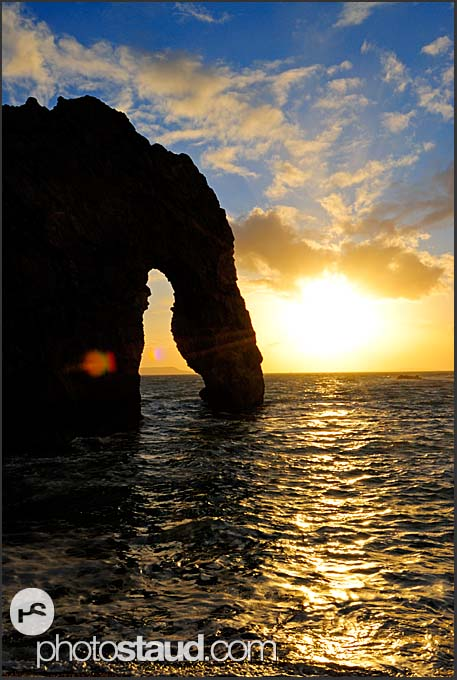 Sun setting at Durdle Door natural limestone arch, Jurassic Coast World Heritage site, Dorset, England, Europe